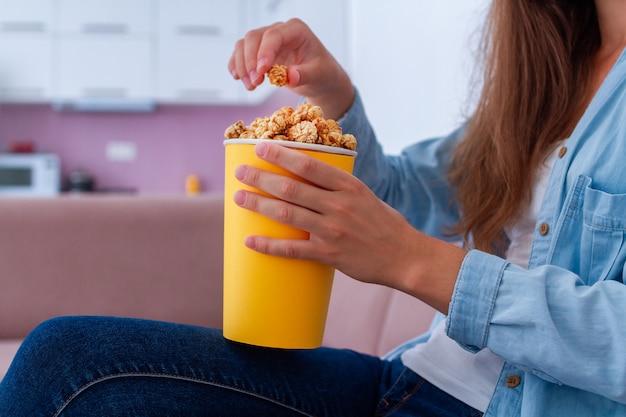 Femme, tenue, manger, caramel, pop-corn, regarder, tv, maison