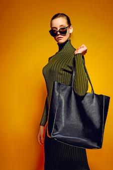 Femme, tenue, noir, cuir, sac