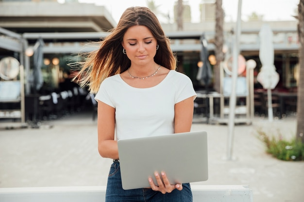 Femme, tenue, ordinateur portable, regarder bas