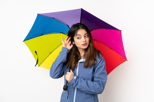 Femme, tenue, parapluie, isolé, blanc, mur, écoute, quelque chose