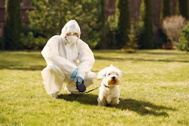 Femme en tenue de protection marchant avec un chien