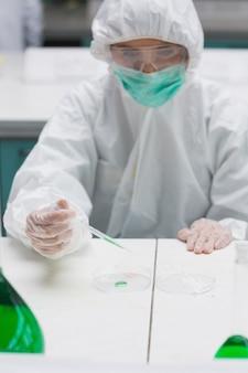 Femme en tenue de protection travaillant avec un liquide vert