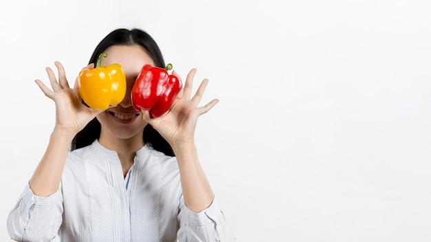 Femme, tenue, rouges, jaune, poivrons, devant, elle, plus, isolé, dans, fond blanc