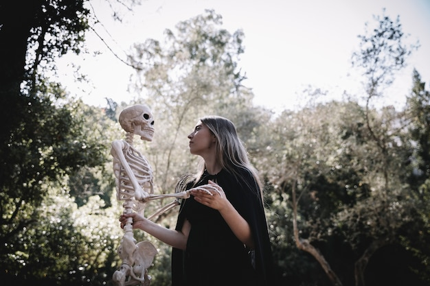 Femme en tenue de sorcier à l'écoute du squelette