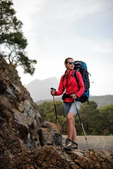 Femme en tenue spéciale debout avec sac à dos de randonnée et bâtons sur le rocher
