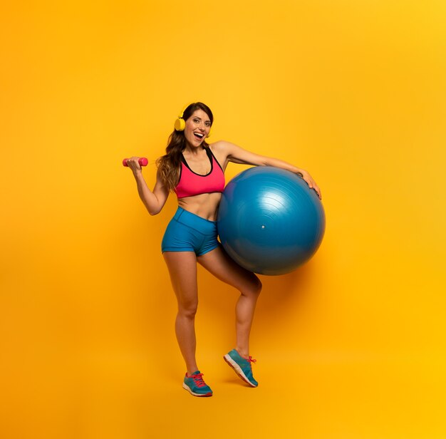 Femme en tenue de sport avec un ballon de gym