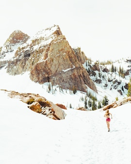Femme en tenue de sport en cours d'exécution dans les champs enneigés avec de hautes montagnes rocheuses