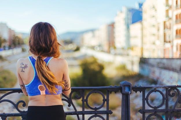Femme en tenue de sport debout au parapet