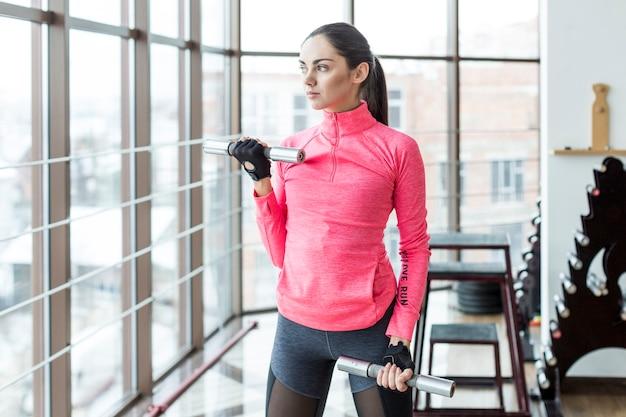 Femme en tenue de sport avec des haltères