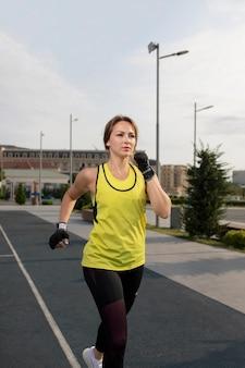 Femme en tenue de sport jaune et noire s'entraînant en courant dans la rue.
