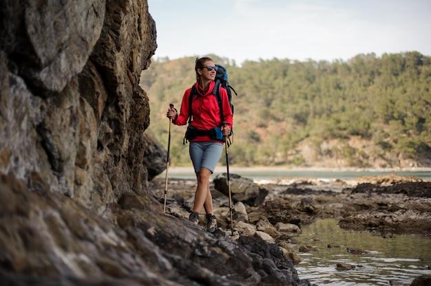 Femme en tenue de sport marchant sur le rocher avec sac à dos de randonnée