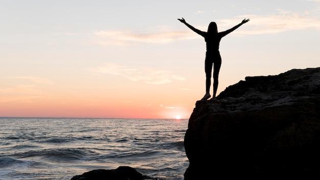 Femme en tenue de sport profitant du coucher du soleil