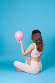 Femme en tenue de sport rose est assise avec son dos ou son demi-côté et tient un ballon