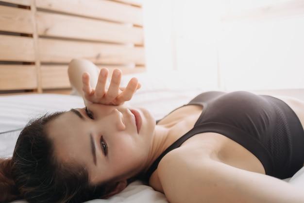Une femme en tenue de sport se repose après l'entraînement dans sa chambre