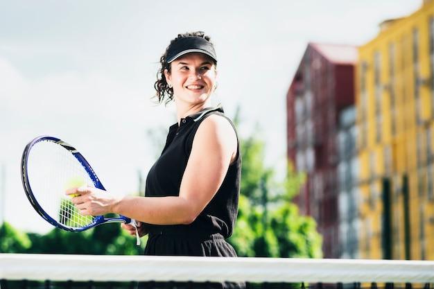 Femme en tenue de sport sert une balle de tennis