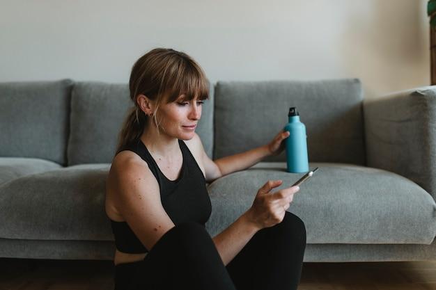 Femme en tenue de sport utilisant son téléphone portable pendant la quarantaine du coronavirus