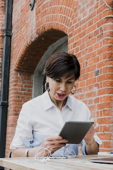 Femme, tenue, tablette, dehors