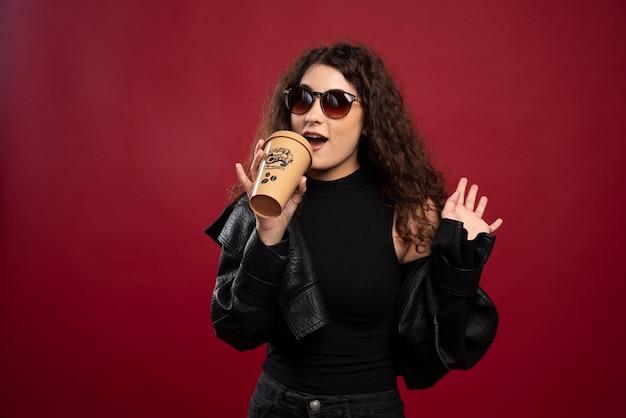 Femme en tenue toute noire posant avec une tasse et des lunettes.