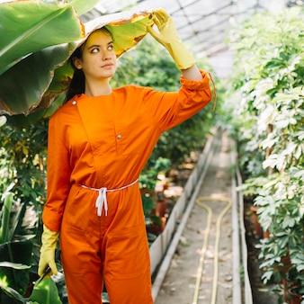 Femme en tenue de travail tenant une feuille de bananier au-dessus de sa tête
