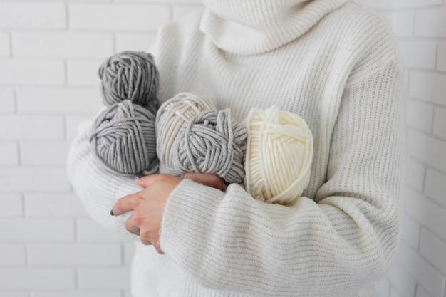 Femme, tenue, tricoter laine, gros plan