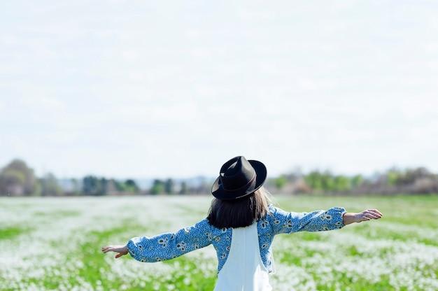 Femme sur le terrain avec un chapeau sur le dos