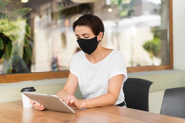 Femme à la terrasse avec tablette portant un masque