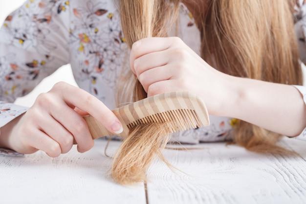 Femme tête chauve, cheveux perdus sur le peigne