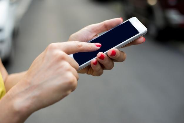 Femme textuelle sur son téléphone portable en plein air