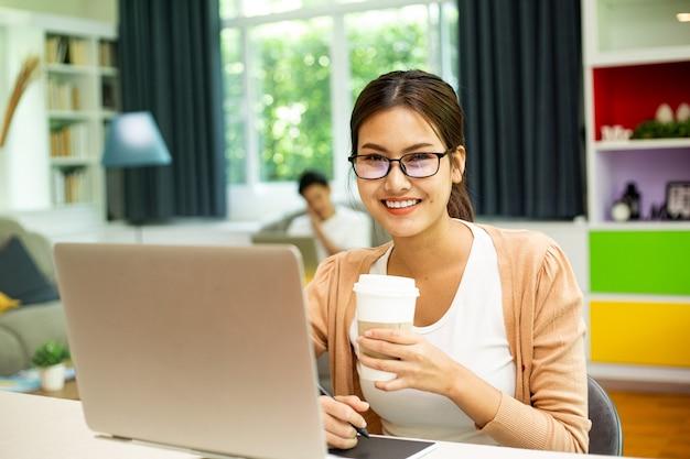 Une femme thaïlandaise asiatique tient une tasse de café en papier pour boire pendant le travail pour rester à la maison. une fille au visage souriant travaille dans le salon.