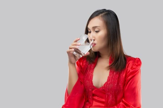 Femme thaïlandaise buvant un verre d'eau avant de se coucher sur un fond gris.