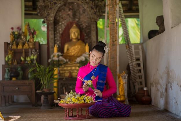 Femme thaïlandaise en costume traditionnel faisant des offres d'encens