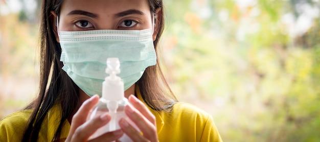 Femme thaïlandaise portant un masque avec sa main tenant un gel d'alcool pour se laver les mains pour prévenir le virus, covid-19