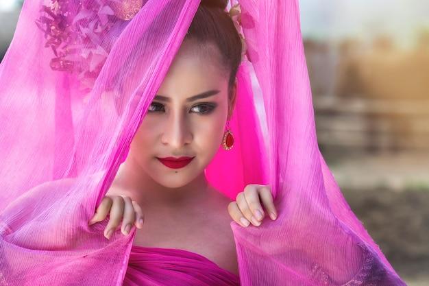 Femme thaïlandaise portant une robe thaïlandaise traditionnelle avec un tissu en soie couvrir sa tête