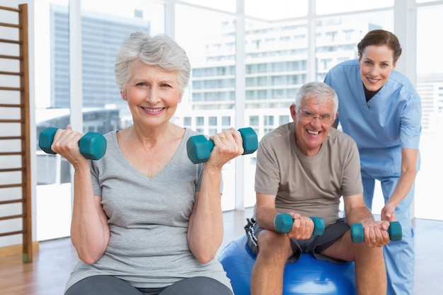 Femme thérapeute aidant le couple de personnes âgées avec des haltères