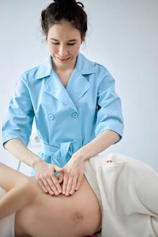 Une femme thérapeute masse les mains d'une femme enceinte, pour un programme de traitement et de détente, lors d'une cure thermale. vue latérale sur le masseur en uniforme bleu massant une femme gravide allongée sur le lit dans une armoire de spa. se concentrer sur le masseur