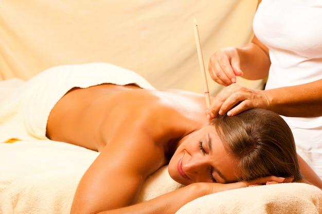 Femme en thérapie avec des bougies d'oreille