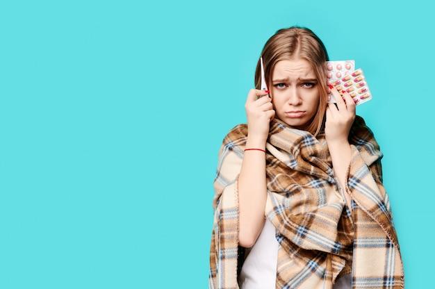 Une femme avec un thermomètre et des pilules dans ses mains s'est enveloppée dans un plaid.