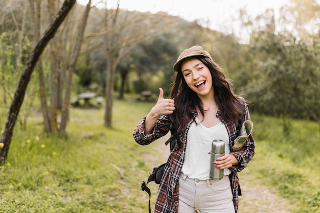 Femme avec thermos gesticulant thumb-up