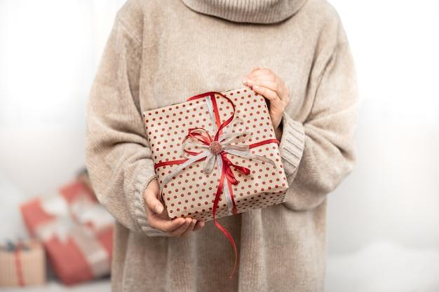 Une femme tient un beau cadeau de noël.