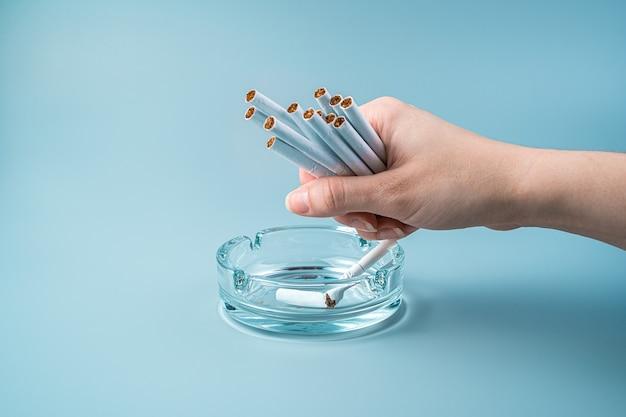 Une femme tient beaucoup de cigarettes dans sa main sur un fond bleu.