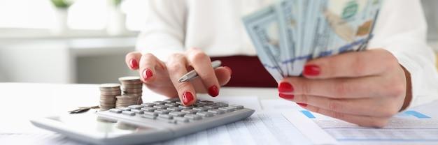 Une femme tient des billets de banque américains dans ses mains et travaille sur une calculatrice calculant le revenu des dépôts