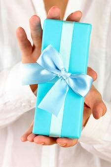 Femme tient une boîte avec un cadeau sur blanc