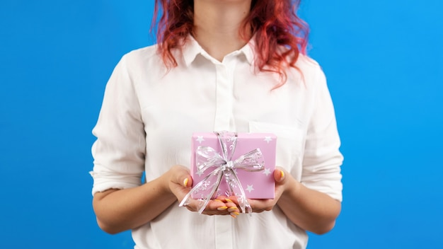 Femme tient une boîte-cadeau sur fond bleu concept de vacances