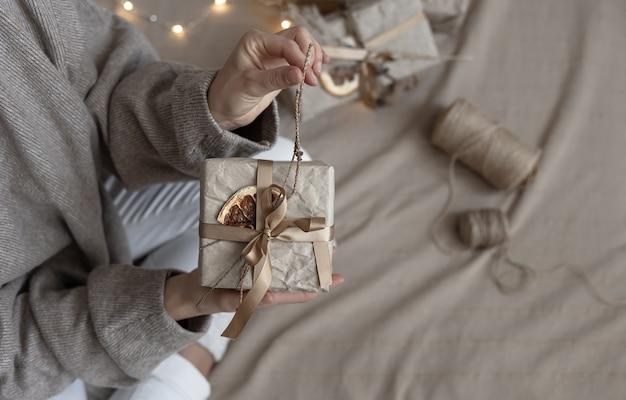 Une femme tient une boîte-cadeau de noël décorée dans un style artisanal, décorée de fleurs séchées et d'une orange sèche, enveloppée dans du papier kraft.