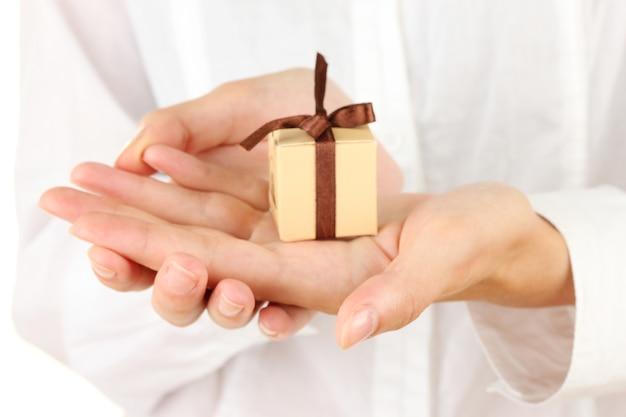 La femme tient une boîte avec un cadeau sur le plan rapproché blanc de fond