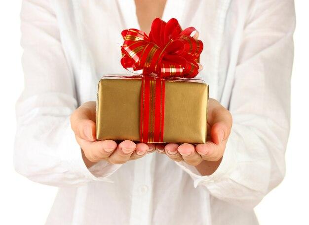 La femme tient la boîte avec le cadeau sur le plan rapproché blanc de fond