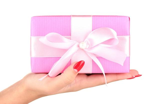 La femme tient la boîte avec le cadeau sur le plan rapproché blanc de mur