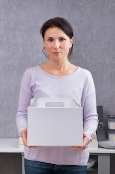 Femme tient une boîte en carton blanc. emballage pour gâteaux et pâtisseries.