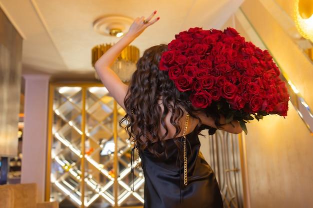 La femme tient un bouquet de luxe de roses rouges.