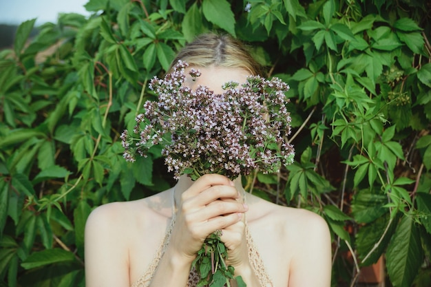 Une femme tient un bouquet de plantes d'origan frais et et cache le visage sur fond de feuilles vertes, mode de vie horizontal à l'extérieur de l'été floral et botanique image photo